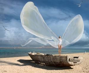 mujer con alas a la orilla del mar